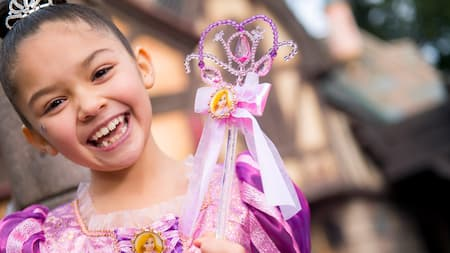 A little girl dressed like Rapunzel holds a scepter featuring a picture of Rapunzel