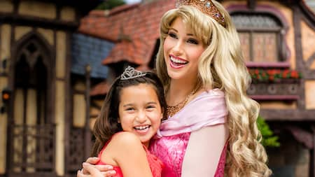 Princess Aurora hugs a girl dressed as a princess