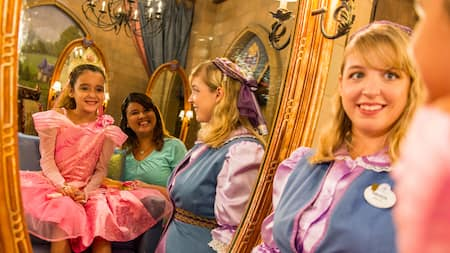 A girl in a princess costume admires herself in a mirror, with her mother and beautician looking on
