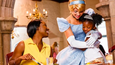 Princess Cinderella hugs a girl as the child's mother looks on