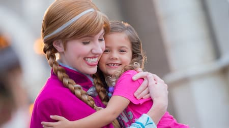 Princess Anna smiles while hugging a small girl