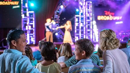 Una familia sonríe mientras miran a artistas en un escenario