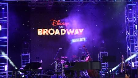 El letrero de Disney on Broadway ilumina un escenario colmado de instrumentos musicales en el Festival of the Arts