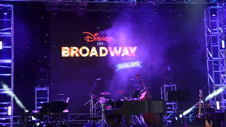 El letrero de Disney on Broadway ilumina un escenario colmado de instrumentos musicales en el Festival of the Arts