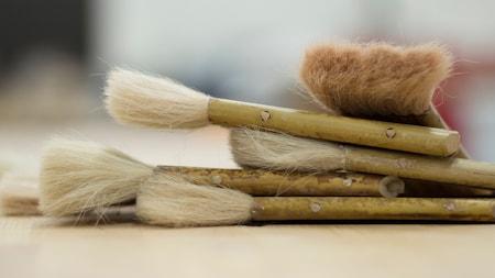 Cinco pinceles de acuarela con cerdas largas y mangos de bambú agrupados en una mesa