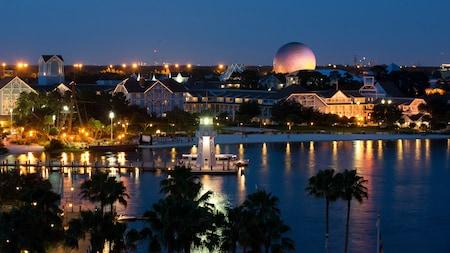 Un faro en un lago cerca de palmeras, un hotel y Spaceship Earth