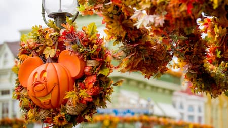 An autumn wreath with a Mickey jack o lantern is tied to the top of an old fashioned street lamp