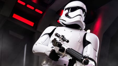 A Star Wars Stormtrooper searches a Star Destroyer with a pointed blaster rifle in hand