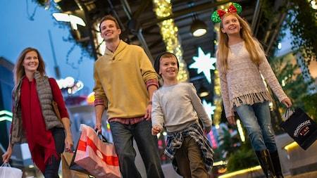 Los 4integrantes de una familia joven sonríen mientras caminan por Disney Springs cargando bolsas de compras