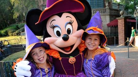 Minnie Mouse fantasiada de bruxa e 2 garotinhas vestindo fantasias de bruxa Minnie