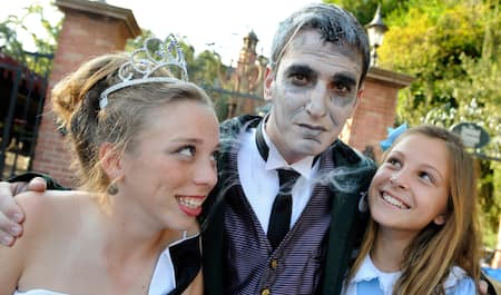 Three teen Guests stand shoulder to shoulder dressed in costumes ranging from a princess, a Ghost Host from the Haunted Mansion and Alice in Wonderland