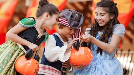 Crianças vestidas como Anna de Frozen, Cinderella e um pirata sorriem após coletarem doces sem alérgenos.