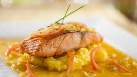 Un plat principal de saumon somptueusement disposé dans une assiette au restaurant avec service à table au Mickey's Not-So-Scary Halloween Party