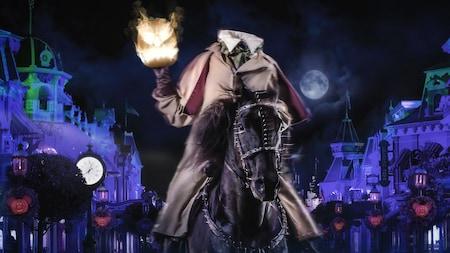 Le cavalier sans tête assis sur un cheval, qui tient une lanterne grimaçante illuminée la nuit lors du Mickey's Not-So-Scary Halloween Party