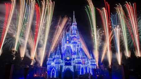 Fireworks flower around Cinderella Caste during Holiday Wishes at Mickey's Very Merry Christmas Party