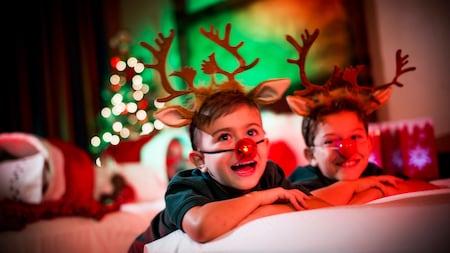 Deux jeunes garçons profitent d'une surprise des Fêtes d'une célébration dans la chambre dans leur hôtel Disney