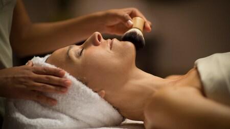 Uma Visitante com a cabeça enrolada em uma toalha e os olhos fechados durante uma experiência de spa