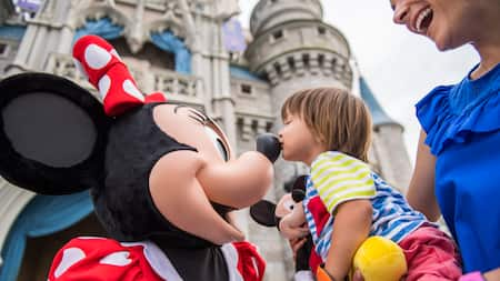 A woman holds a child that is kissing Minnie Mouse's nose
