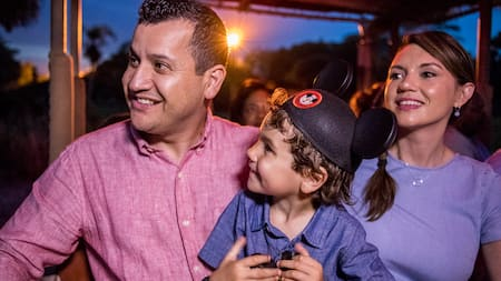 A man and a woman smile while holding a boy wearing Mickey Ears