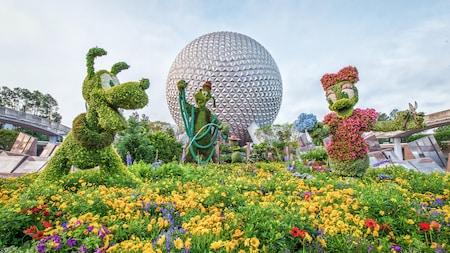 Arbustos artísticos en forma de Goofy, Pluto y Daisy frente a Spaceship Earth