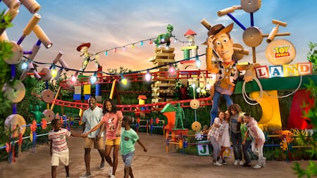 2 families stand near a statue of Woody and the sign for Toy Story Land