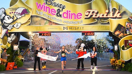 The first runner crosses the finish line during the Disney Wine & Dine Half Marathon Weekend