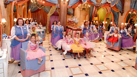 Several girls dressed as princesses with their stylists in the salon at Bibbidi Bobbidi Boutique