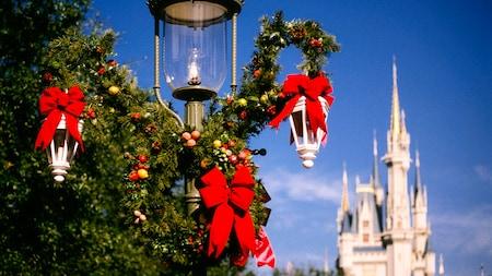 Primer plano de un farol decorado con cintas navideñas y vegetación, con el Cinderella Castle de fondo