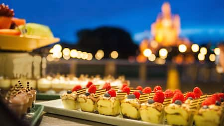 Trays of assorted desserts on a table in an open-air dining venue