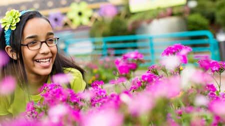 A smiling girl wearing glasses and a floral headband sits within a garden exhibit