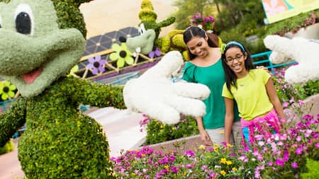 Female Guests smile while viewing an enchanting Mickey Mouse topiary display