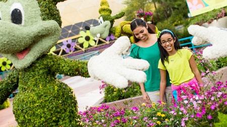 Visitantes do sexo feminino sorriem em uma exibição encantadora de topiarias do Mickey Mouse