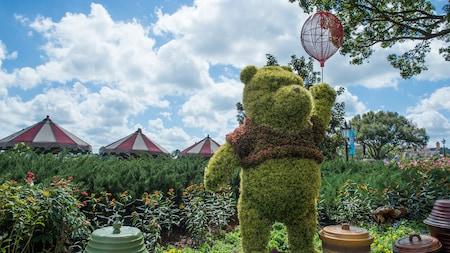 Un arbusto ornamental con forma de Winnie the Pooh sosteniendo un globo tejido, ubicado en un jardín exuberante