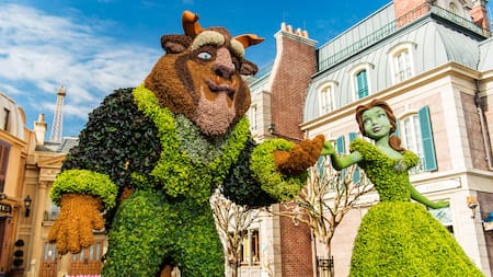 Arbustos artísticos de Belle y Beast cerca de edificios de piedra