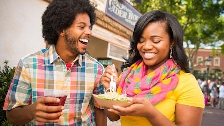 Un joven sonriente sostiene una bebida mientras una joven prueba un plato de vegetales