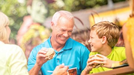 Un niño y sus abuelos disfrutan los sándwiches de cerdo desmenuzado en una mesa al aire libre