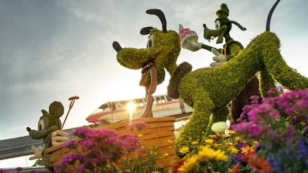 Arbustos ornamentales de Mickey, Pluto y Goofy en un jardín con temática de pícnic y un monorriel a la distancia