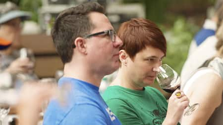 A woman holds a glass of wine to her nose to smell the aroma