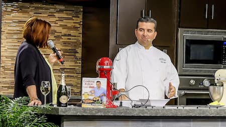 A woman with a microphone speaking to Chef Buddy Valastro in a demonstration kitchen containing a mixing machine and one of the chef's cookbooks