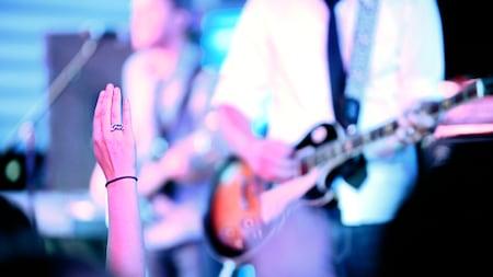 Mulher com o braço para cima enquanto um músico toca guitarra.
