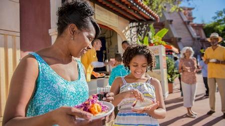 Uma mulher e uma menina seguram pratos de comida em um festival ao ar livre