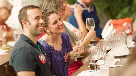 Homem e mulher sorriem com amostras de vinhos em um evento de degustação