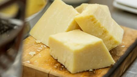3 blocks of dry aged cheese on a cutting board