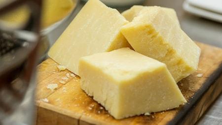 3bloques de queso seco curado en una tabla de cortar