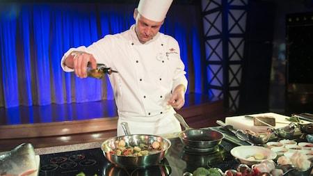 Un chef dans une cuisine de présentation verse de l'huile dans une sauteuse contenant des pétoncles et des légumes