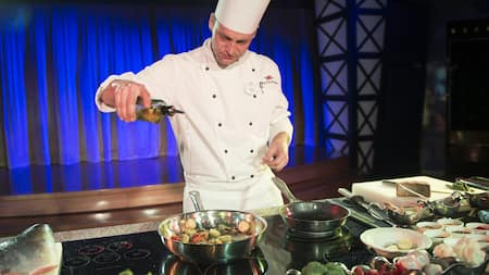 A chef in a demonstration kitchen pours oil into a sauté pan containing scallops and vegetables