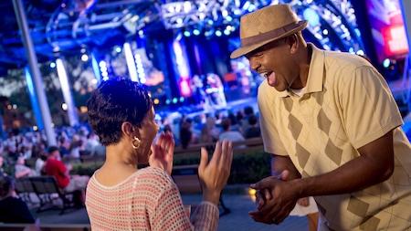 Homem e mulher sorriem animados, enquanto apreciam o show ao vivo e ao ar livre