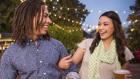Una pareja joven y sonriente disfruta una cerveza y las festividades al aire libre