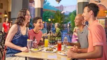 Em uma mesa ao ar livre cercada por outros comensais e palmeiras, um casal e seus 2 filhos adolescentes sorriem e conversam enquanto saboreiam bebidas e pratos de aparência deliciosa, em meio a uma decoração de estilo marroquino