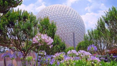 Spaceship Earth asciende al cielo entre medio de flores y exuberante vegetación en Epcot